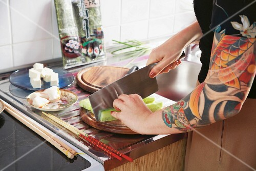 A woman with a tattooed arm preparing sushi in a kitchen
