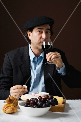 A stereotypical French man drinking red wine with a cheese platter