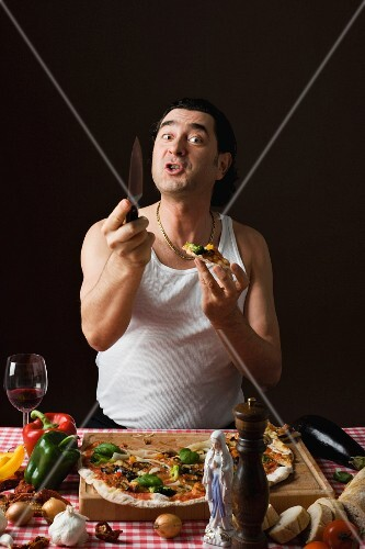 A stereotypical Italian man with a knife and a pizza