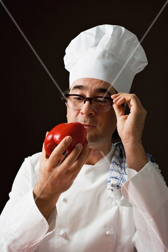 A stereotypical chef holding a red pepper