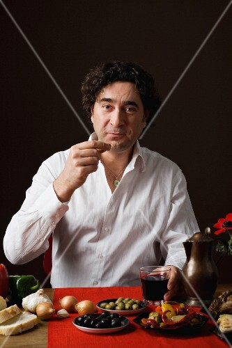 A sterotypical Spanish man eating tapas