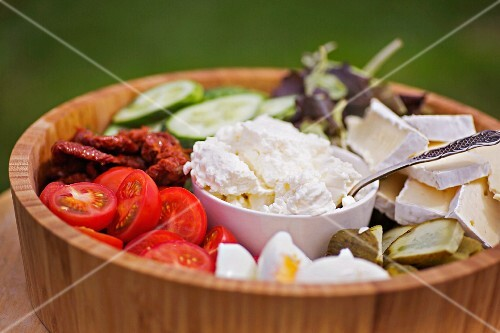 A wooden bowl filled with various salad ingredients (tomatoes, cucumber, goat's cheese and Brie)