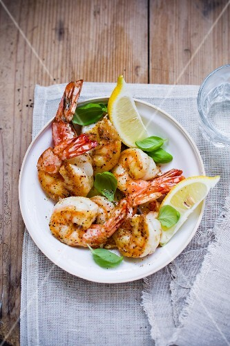 Fried prawns with basil and lemon wedges