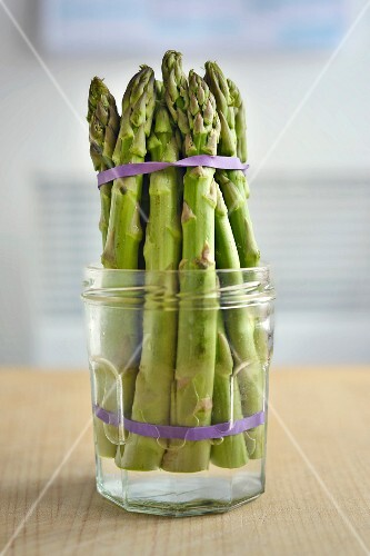 Keeping asparagus fresh: green asparagus spears in a glass with a little water