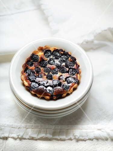 A cherry tartlet dusted with icing sugar on a stack of plates