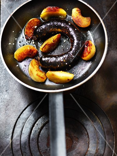 Fried blood sausage with apple wedges in a pan