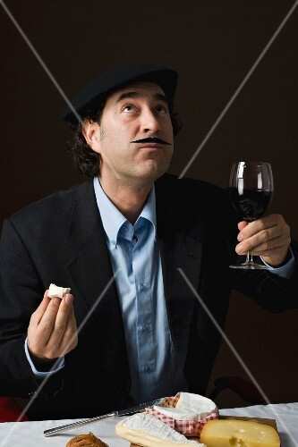 A stereotypical Frenchman drinking red wine with a cheese platter