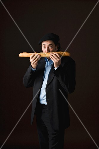 A stereotypical Frenchman sniffing a baguette
