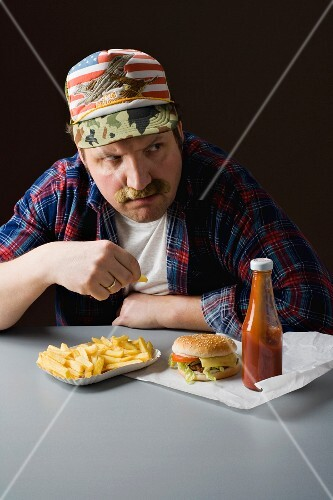 A stereotypical American man eating fast food