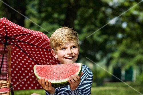 A young boy holding a slice of watermelon at a picnic