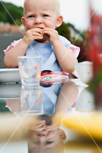A toddler eating at a garden table