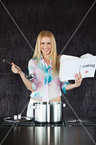 A happy woman with a cookbook and a ladle in front of a stove