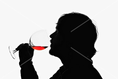 A man drinking a glass of red wine