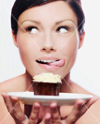 A woman holding a cupcake on a plate and licking her lips