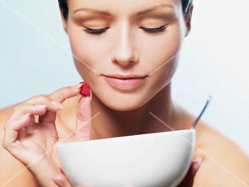 A woman holding a raspberry above a muesli bowl
