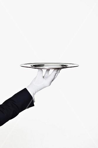 A butler holding an empty silver tray
