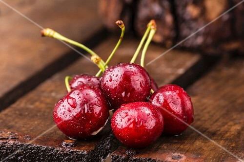 Freshly washed cherries on a wooden crate