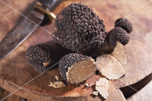 Black truffles, sliced, on a chopping board