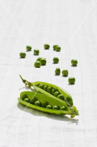 Pea pods and peas on a white surface