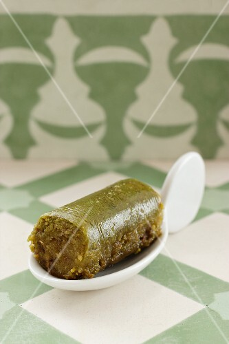 A green baklava roll on a canapé spoon