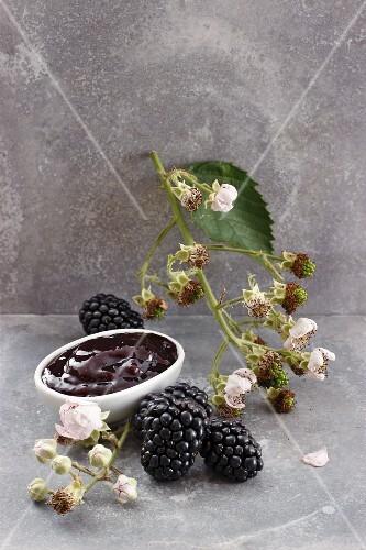A bowl of blackberry jam, blackberries and blackberry sprig