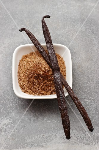 Brown vanilla sugar in a bowl with two vanilla pods