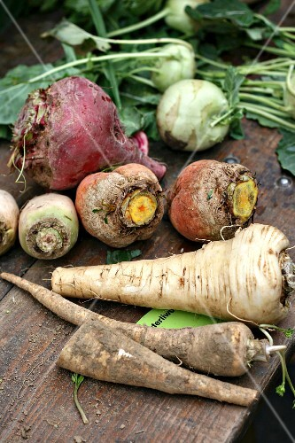 Various root vegetables and kohlrabi on a wooden table