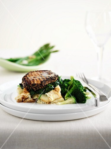 A peppered steak with mashed potatoes and broccoli