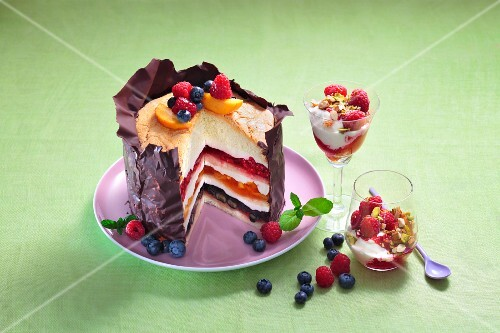 A festive fruitcake with a crispy chocolate coating next to glasses of peach Melba with raspberries