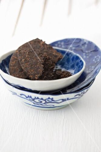 A piece of a pu-erh tea brick in a blue-and-white bowl