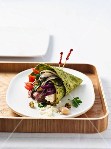 A spinach and herb wrap with lamb, pistachios and feta cheese