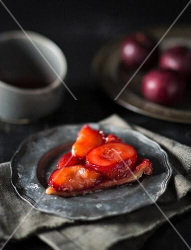 Plum tarte tatin on a pewter plate