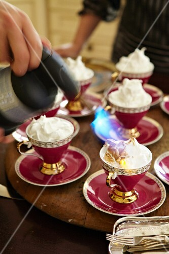 Meringue being browned with a blowtorch