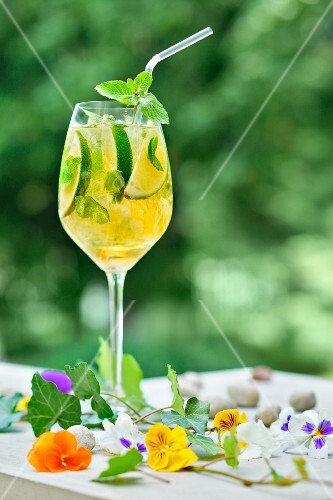 A glass of lemonade made with limes, mint and edible flowers on a garden table