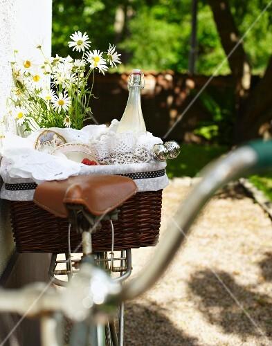 Strawberries and lemongrass lemonade in picnic basket on bicycle in garden