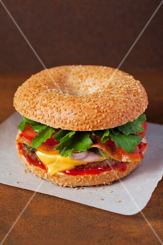 A cheeseburger on a sesame seed bagel