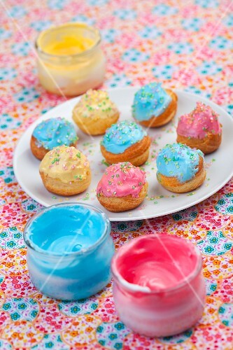 Profiteroles with colourful icing and sugar sprinkles