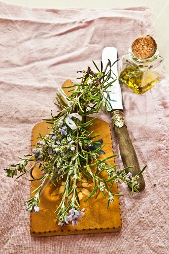 Rosemary oil in front of flowering rosemary on a wooden board