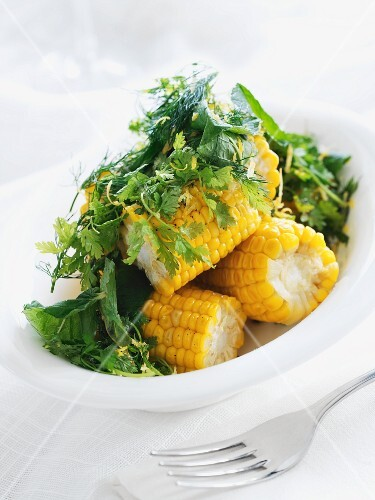 Corn on the cob with butter and fresh herbs