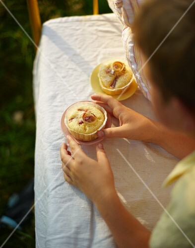 A boy eating a muffin for breakfast in bed in a field