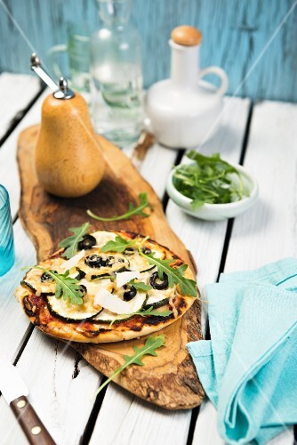 A mini vegetable pizza with olives and rocket