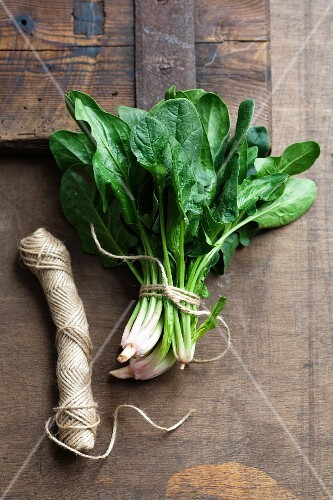 Fresh spinach leaves tied with kitchen twine on a wooden surface