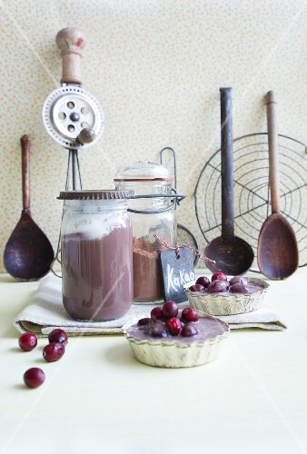 Jars of chocolate pudding with cream and cranberries in chocolate sauce