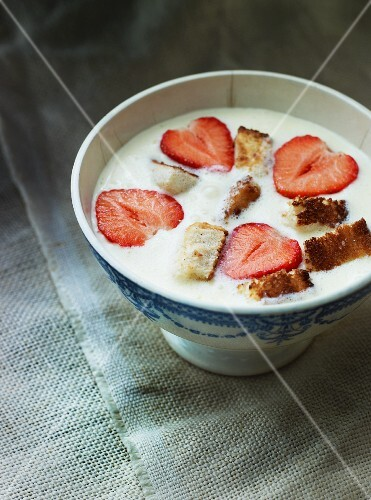 Pieces of cake and strawberries in milk cream