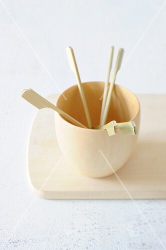 Mini wooden skewers in a wooden cup
