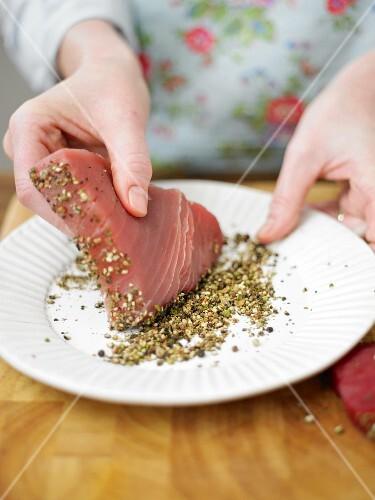 Tuna fish steak being coated in peppercorns