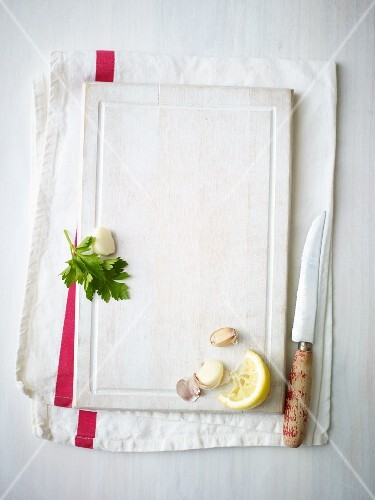 A lemon wedge, garlic cloves and parsley on a white chopping board