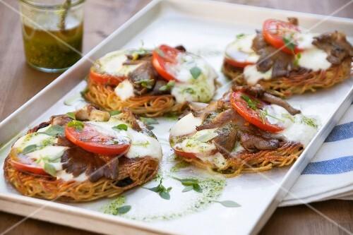 Spaghetti pizzas topped with mushrooms and mozzarella