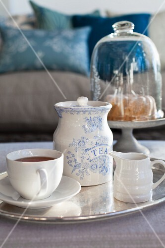 Teacup, milk jug and tea caddy on silver tray with cake under glass cover in background