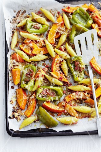 Potato orzo pasta with caramelised pumpkins and peppers on a baking tray